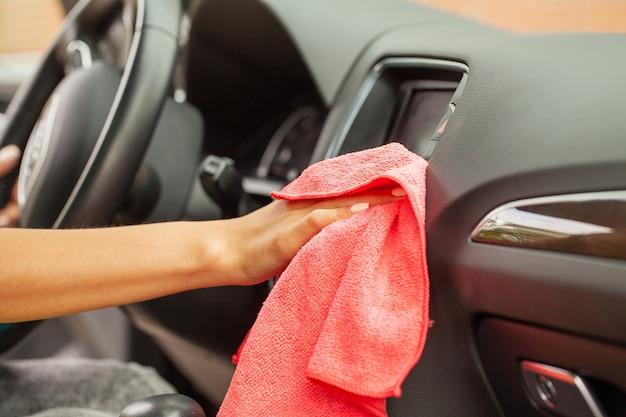 Main avec un chiffon en microfibre de nettoyage intérieur de voiture moderne.