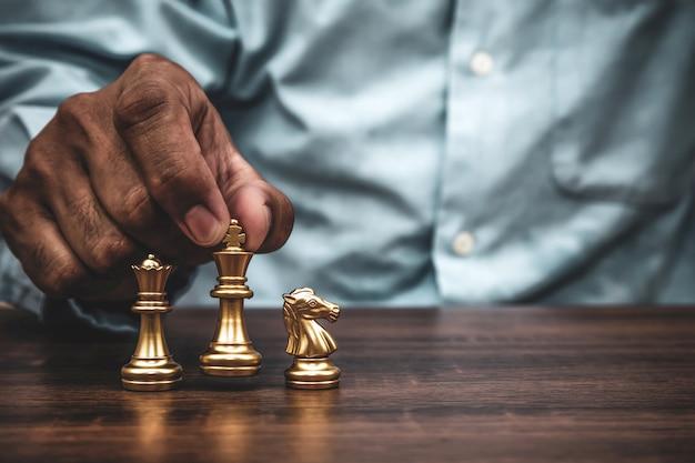 Main choisir le travail d'équipe du stand d'échecs roi sur l'échiquier.