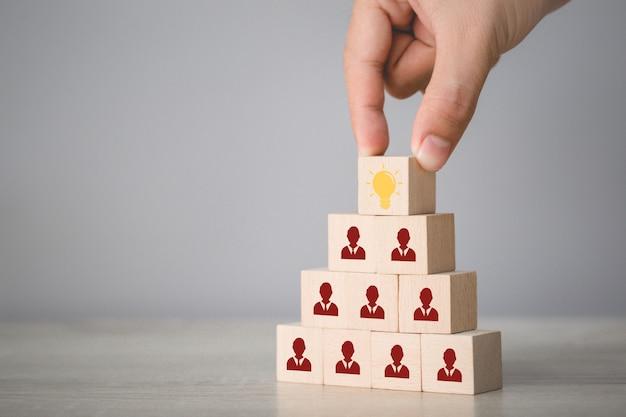 Main en choisissant le cube en bois avec l'icône ampoule et symbole humain, idée créative et concept d'innovation.