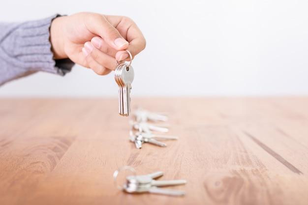 Main choisissant ensemble de clé d'argent à la maison