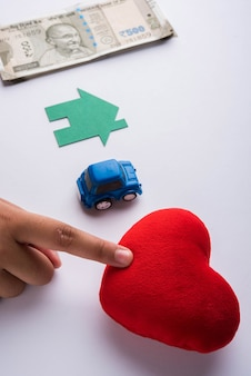 Main choisissant entre l'argent indien, la maison, la voiture et l'amour ou les soins de santé