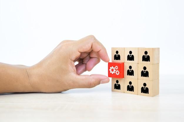 Main choisissant l'icône du rouage avec le symbole des personnes sur la pile de blocs en bois.