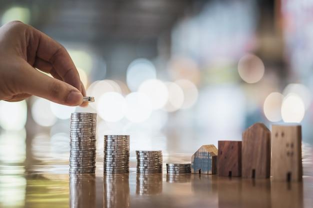 Main en choisissant la ligne de monnaie sur la table en bois et mini maison en bois,