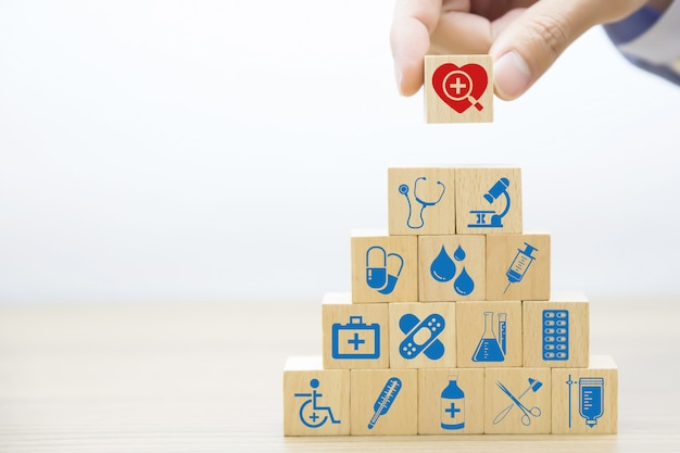 Main, choisissez des icônes médicales et de santé sur bloc en bois.