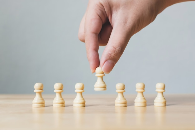 Main choisit un jeu d'échecs en bois se démarquant de la foule