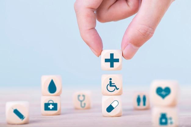 Main choisit un symbole médical de soins de santé icônes émoticônes sur bloc de bois