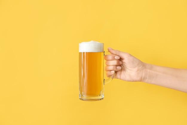 Main avec chope de bière sur la couleur