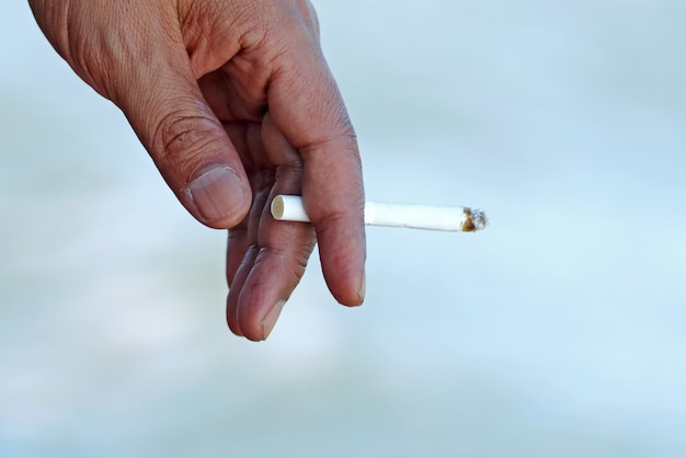 Main avec cigarette allumée