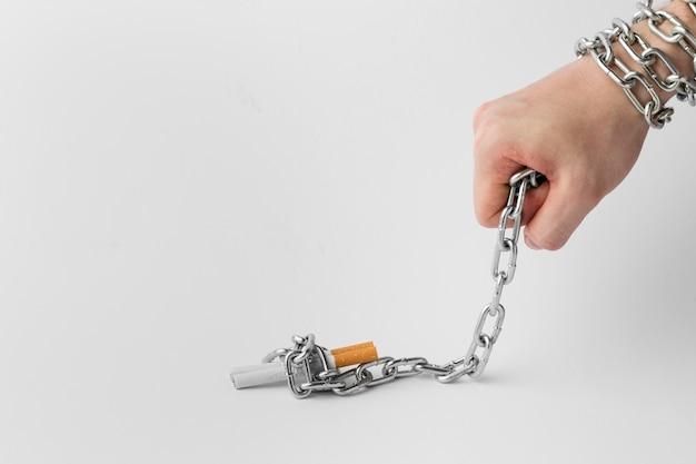 Main avec cigarette en chaîne