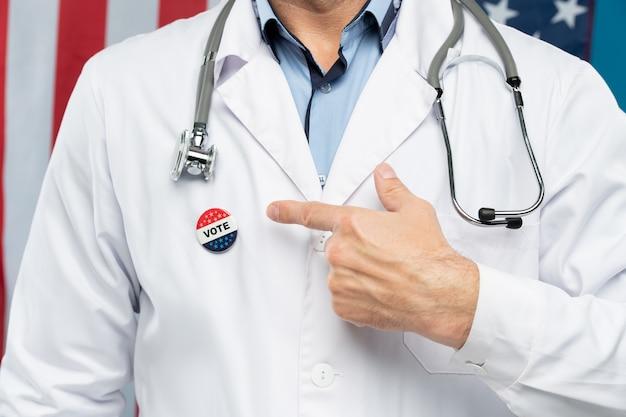 Main d'un citoyen américain contemporain en uniforme de médecin pointant l'insigne sur sa poitrine, ce qui signifie qu'il va voter