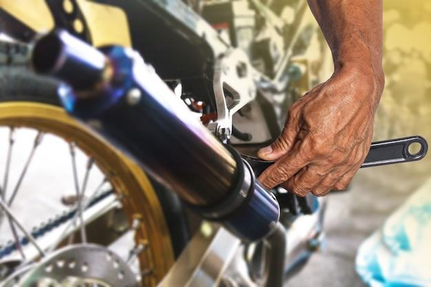 Main avec clé, réparation mécanique professionnelle et modifications à la moto