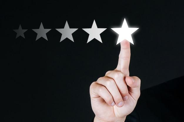 Main de client d'affaires appuyant sur le bouton cinq étoiles sur l'écran visuel sur fond noir