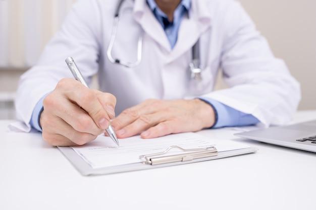 Main de clinicien professionnel avec stylo sur presse-papiers avec document médical va prendre des notes ou une ordonnance