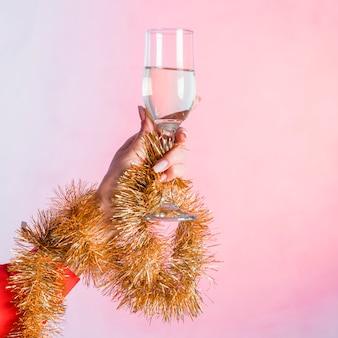Main avec des clinquant d'or tenant un verre de champagne