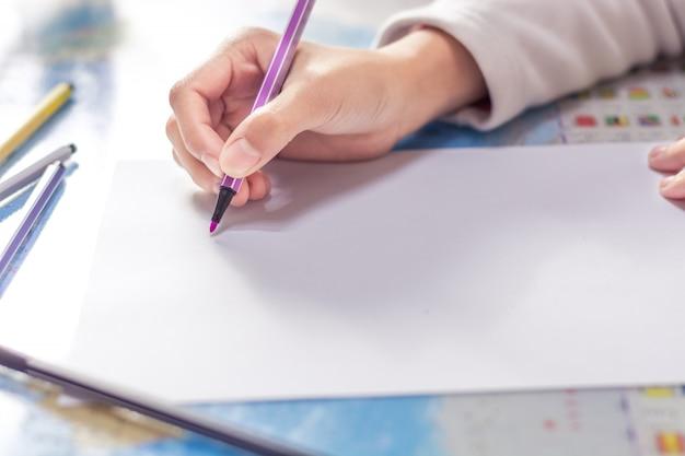 Main close-up de l'élève tenant un crayon