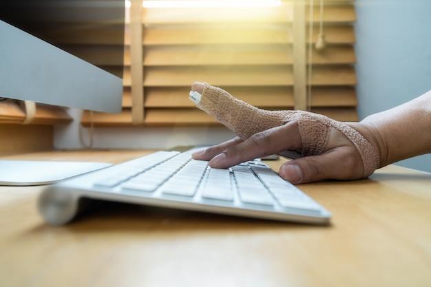 Main closeup avec poignet de déversoir à travailler avec le clavier de l'ordinateur