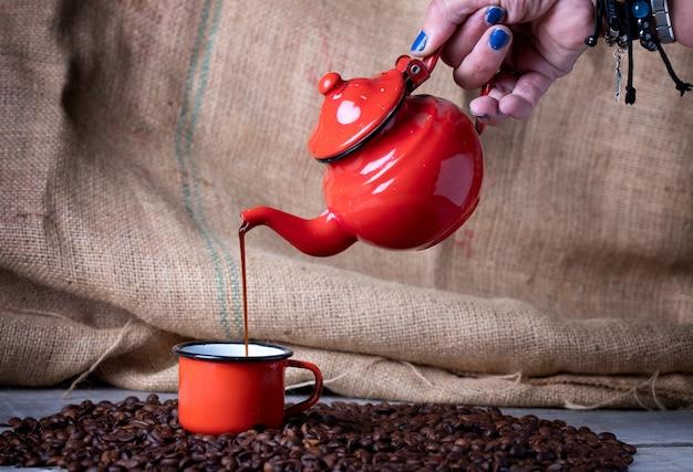 Main avec des clous bleus avec une théière en métal rouge faisant le café dans une tasse en métal rouge