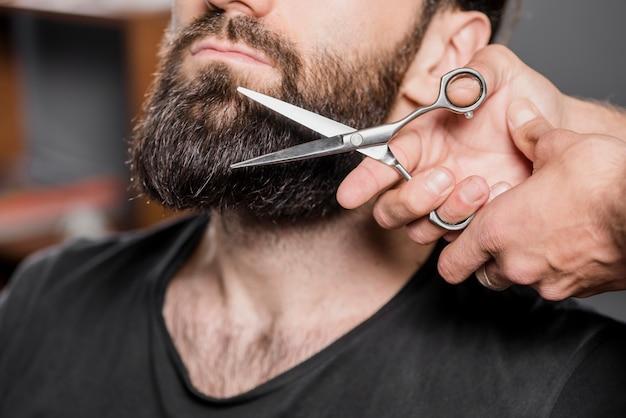 La main de coiffeur coupe la barbe de l'homme avec des ciseaux