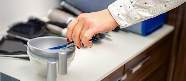 Main de coiffeur prépare le colorant dans un bol pour la coloration des cheveux dans un salon de coiffure