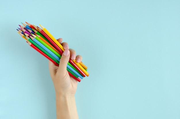 Main avec composition de crayons de couleur sur fond bleu.