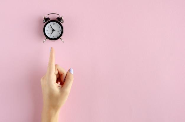 Main avec composition réveil analogique sur fond rose.