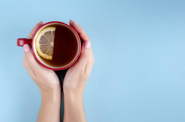 Main avec composition de tasse de thé rouge et citron tranche sur fond bleu.