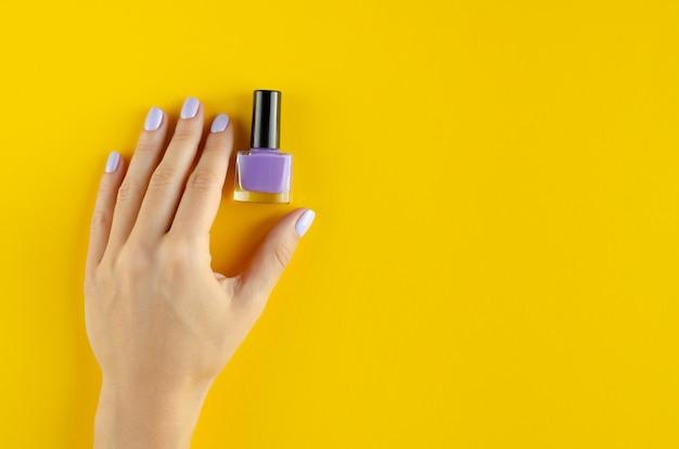 Main avec composition de vernis à ongles violet sur fond jaune.
