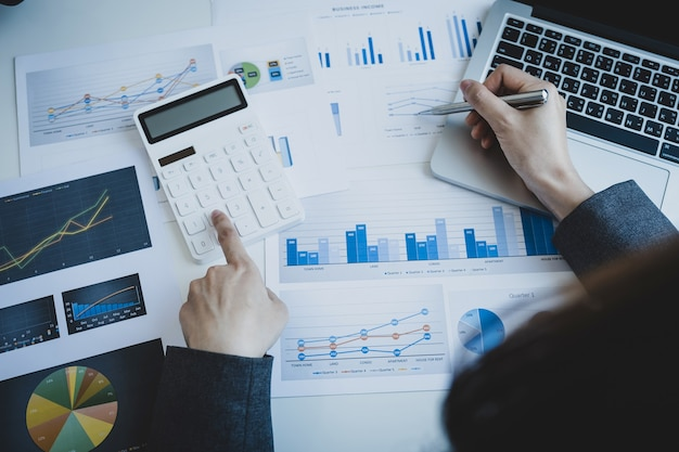 La main de comptable de femmes d'affaires tenant le stylo utilise la calculatrice et l'ordinateur portable faisant le compte
