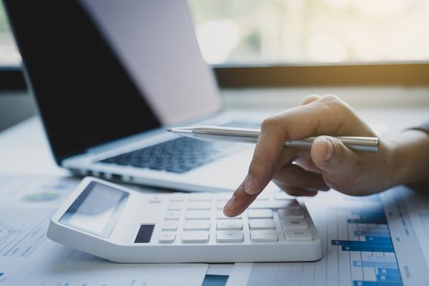 La main de comptable de femmes d'affaires utilise une calculatrice et un ordinateur portable faisant un compte
