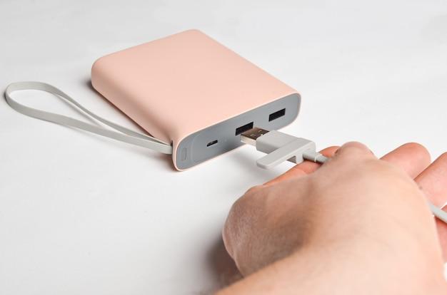 Une main connecte un câble usb à une banque d'alimentation sur fond blanc. batterie externe.
