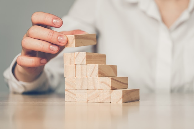 Main construit une échelle à partir de blocs de bois