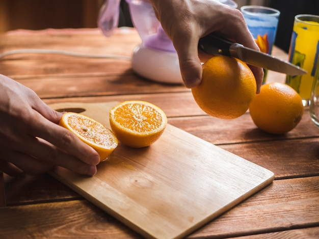 Main coupant des oranges fraîches avec un couteau sur une surface en bois pour faire un jus de fruits