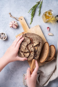 Main coupe le pain de seigle sur une planche de bois avec du romarin, de l'ail et de l'huile d'olive. vue de dessus