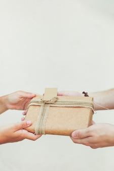 Main de couple tenant cadeau sur fond uni