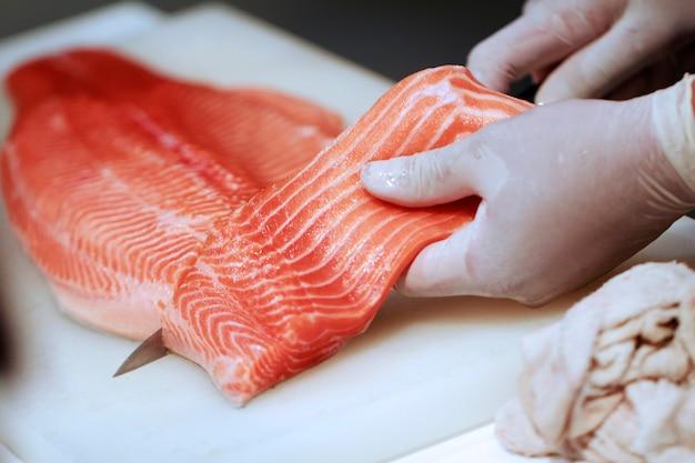 Main avec un couteau coupe le poisson saumon.le poisson cru sur la plaque de cuisson. le chef prépare du poisson cru pour le jap