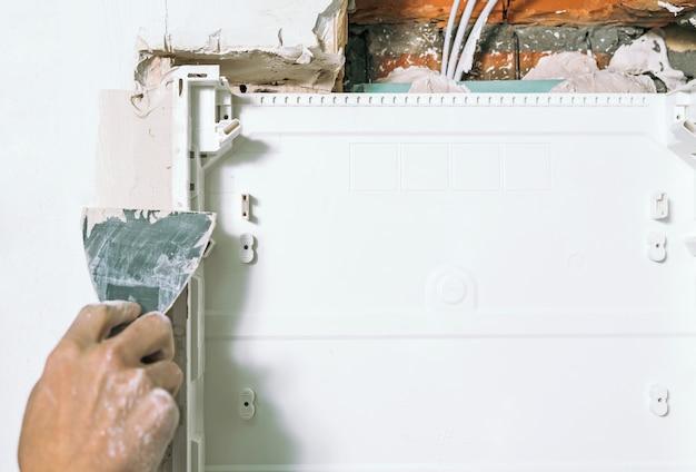 La main avec un couteau à mastic montre comment cacher le point de connexion entre deux morceaux de murs secs à l'aide de mastic