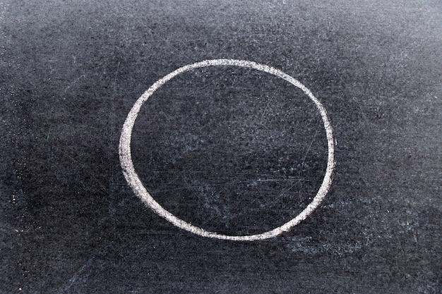 Main de craie blanche, dessin en cercle ou forme ronde sur fond de tableau noir