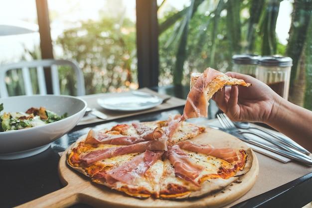 Une main cueillant un morceau de pizza au jambon de parme pour manger au restaurant