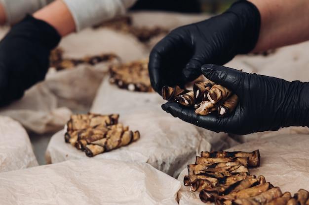 Main de cuisinier professionnel portant des gants servant une assiette avec un plat de collations délicates prêt pour la fête