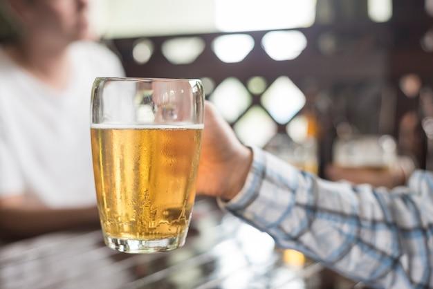 Main de culture tenant la tasse de bière froide