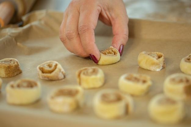La main de la dame pose des petits pains à la cannelle sur une plaque à pâtisserie tapissée de papier sulfurisé
