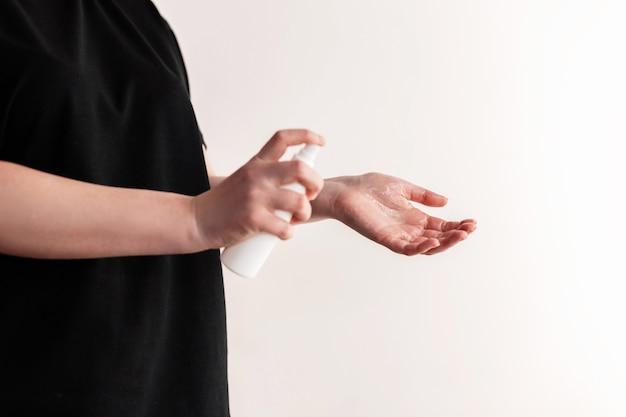 Main de dame qui applique un spray d'alcool ou un spray antibactérien pour empêcher la propagation des germes, des bactéries et des virus