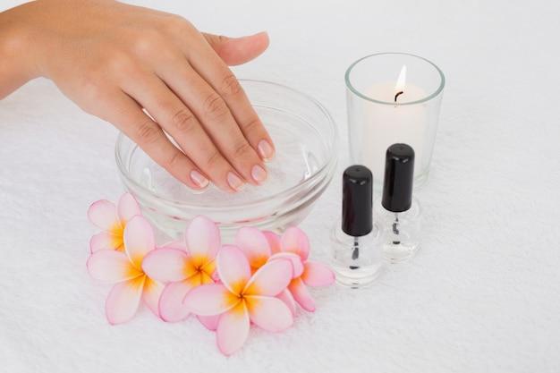 Main dans un bol le long des fleurs et des bougies