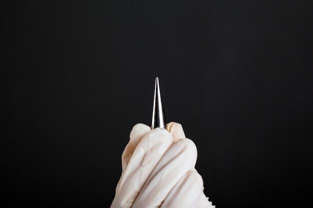 Main dans un extenseur d'oreille de gant jetable blanc pour percer des tunnels sur un fond sombre