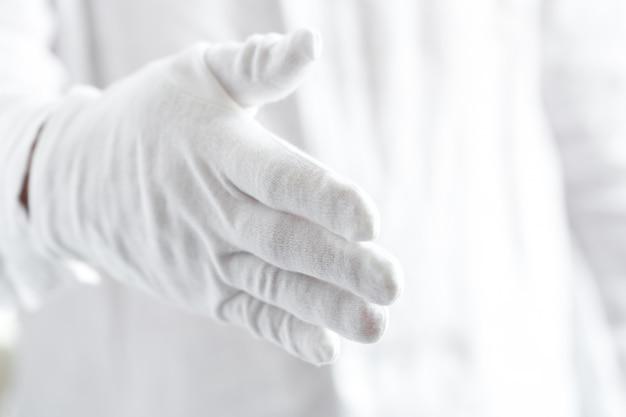 Une main dans un gant blanc est prête à trembler