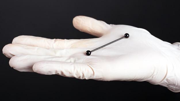 La main dans un gant blanc est titulaire d'un cartilage piercing oreille bijoux couleur noire sur noir