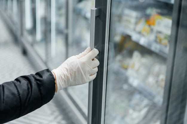 La main dans un gant blanc ouvre une porte de vitrine. sécurité épidémique