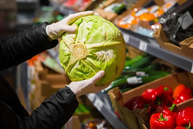 La main dans un gant blanc prend du chou dans un magasin. sécurité épidémique