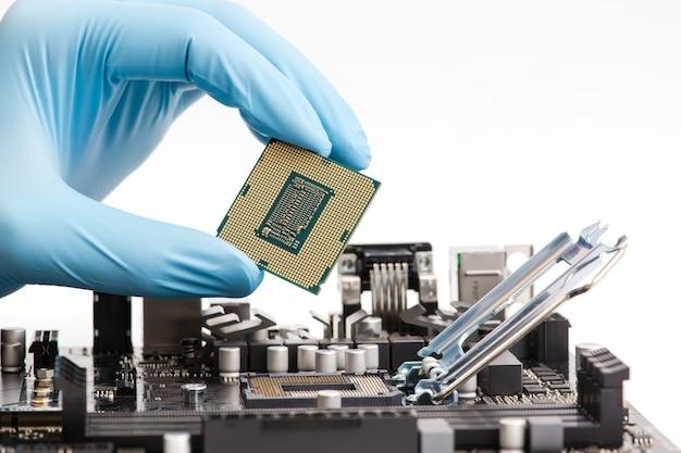 Main dans un gant bleu en caoutchouc avec un composant informatique principal carré lors de l'assemblage de la construction de la machine.