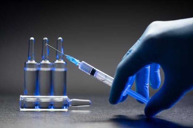 Main dans un gant bleu médical tenant une seringue sur fond gris.
